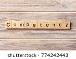 Small photo of Competency word written on wood block. Competency text on table, concept.
