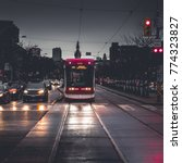 Small photo of Toronto streetcar stopped at red light in downtown traffic at nightfall. Face-on view of train from tracks. Toronto, Ontario, Canada
