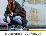 Small photo of Close-up of smiling young girl smoking a cigarette against concrete wall. Rebellious adolescence concept.