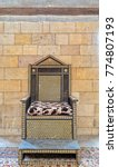 Small photo of Wooden chair with arabesque seamless pattern based on hexagram (star of David) on stone bricks wall