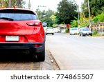 closeup red car on the road... | Shutterstock . vector #774865507