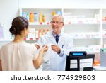 Small photo of medicine, pharmaceutics, healthcare and people concept - senior apothecary with drug and female customer at pharmacy