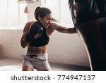 female boxer hitting a huge...   Shutterstock . vector #774947137