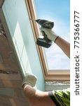 Small photo of Worker installing the gypsum plaster boards near Plastic (mansard) or skylight window in attic room