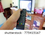 hand holding tv remote control... | Shutterstock . vector #775415167