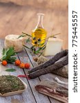 Small photo of several variety of traditional Corsican charcuterie on a wooden background with an olive branch and black olives