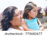 sad latin woman with her little ... | Shutterstock . vector #775682677