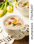 Small photo of Traditional Polish white borsch with Easter decoration. Front view.