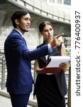 Small photo of Two young confident business people dressed in classical style discussing new business strategy and office building on background. Businessman and woman discuss work in city outdoor on building