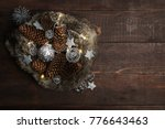Small photo of Christmas concept with pinecones, ornaments and lights in warm pelage with copy space, top view