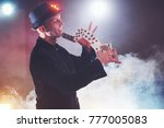 Small photo of Magician showing trick with playing cards. Magic or dexterity, circus, gambling. Prestidigitator in dark room with fog.