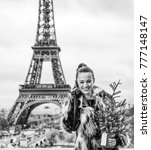 Small photo of The Party Season in Paris. smiling modern fashion-monger with Christmas tree in fur coat against Eiffel tower in Paris, France talking on a mobile phone