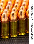 Small photo of 9mm full metal jacket pistol cartridges on a carbon fiber background