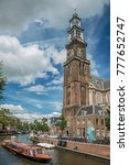 Small photo of Amsterdam, northern Netherlands - June 26, 2017. Canal with old brick steeple church, boats and sunny blue sky in Amsterdam. Famous for its huge cultural activity, graceful canals and bridges.