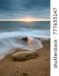 Small photo of Beautiful sunset landscape image of Burton Bradstock golden cliffs in Dorest England