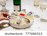 woman's hand with oysters and... | Shutterstock . vector #777684313