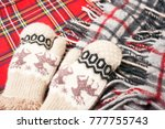 Small photo of Woolen warm mittens and warm scarf on a red background. In anticipation of cold weather.