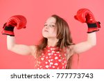 Small photo of Child flex arms with muscle, biceps, triceps in boxing gloves. Kid boxer with long hair on red background. Girl power, feminism concept. Sport, energy, activity. Victory, champion, winner.