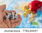 Small photo of A man throws dice with red and blue markings on the world map. World order, map and money.