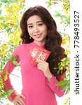 Small photo of Waist-up portrait of pretty Asian woman with long curly hair posing for photography while holding red envelopes presented for Lunar New Year in hand, white background decorated with ochna trees