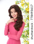 Small photo of Portrait shot of joyful Vietnamese woman wearing elegant pink dress posing for photography with charming smile, white background decorated with blooming ochna tree