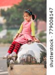 Small photo of GUANGZHOU-DEC. 13, 2009. Adorable young girl on a chrome sphere. China has a traditional bias for sons. Many families abort female fetuses and abandon baby girls to ensure their one child is a son.