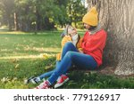 Small photo of Portrait of attractive female model, has pleasant conversation with daughter, rest on green grass, look happily, have joy. Lovely woman with small girl sit on ground, admire autumn and fresh air
