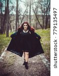 Small photo of A pretty goth redhead in a green coat on a forest path