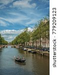 Small photo of Amsterdam, northern Netherlands - June 26, 2017. Canal with old brick buildings, bridge, boat passing by and blue sky in Amsterdam. Famous for its huge cultural activity, graceful canals and bridges.