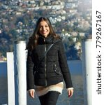 Small photo of Sweet young woman with winter clothes walking on pier gangway of Lake Lugano with mountains on the background and flare sun light, Switzerland
