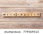 Small photo of Myth reality word written on wood block. Myth reality text on table, concept.