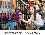 Stock photo portrait of happy woman selecting collars and leads in petshop 779712517