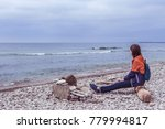 Beautiful view of rocky coast on Gotland, island in the Baltic Sea in Sweden. Girl sitting on a log, looking into the distance. Tourist is by fireplace made of stone. Camp on stone shore. Cloudy day.