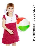 Small photo of A little fair-haired girl with pigtails and a short bangs, in a short, red summer dress.She plays with a large striped inflatable ball.