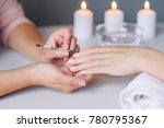 Small photo of Nail care. Closeup of beautiful woman hands getting manicure in spa salon. Female manicurist cleaning cuticle with professional manicure pusher tool. Cosmetic procedure.