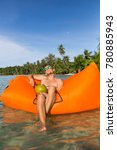 Small photo of Young blonde man, boy at the beach with Lazy Inflatable Air Bed, hammock, couch camping. Lounger Sofa Beach Chair Portable Sleeping Bag Mattress. Relax, vacation, travel. Coconut, sun glasses, hat