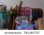 Old household goods. Old Household stuffs for house keeping. Brooms, dirty rags, red chairs, green basket, red table and other miscellaneous items.
