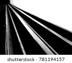 Small photo of Black and white high contrast image of leading straight lines running diagonally starting broad and then converging far away forming a straight path and with blown out background and dark foreground