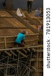 Small photo of Reckless construction worker working at height without any protection or body harness equipment