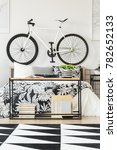 Small photo of Black and white geometric rug in modern teenager bedroom with bike above bed and botanic accent