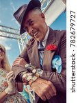 Small photo of London, England, 05/05/2017, A man in 1920s fancy dress as a mobster mafia con artist seller of fake and stolen goods on his wrist. Handsome and untrustworthy street trader. Fashionable pin stripe