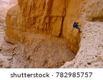 Small photo of Middle aged female climber use technique of the abseil method of roping down. Canyoning in dry wadi of Judaean desert, Israel