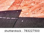 Small photo of Closeup of overlapping black asphalt shingles and underlying oriented strand board subroof material