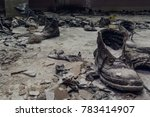 Small photo of Old shoes on a dusty floor in a war-torn house, ruined dark building inside interior, aftermath of disasters concept, toned
