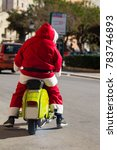 Small photo of Santa Claus dressed man riding a motorcycle in a urban context
