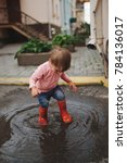 Small photo of girl plays in the puddle outdoors