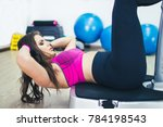 Small photo of Young women training Crunches on vibrate plates.
