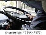man driving a city bus through... | Shutterstock . vector #784447477