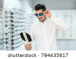 man trying on sunglasses in... | Shutterstock . vector #784635817