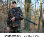 Small photo of Hunter in camo suit with double barrel shotgun